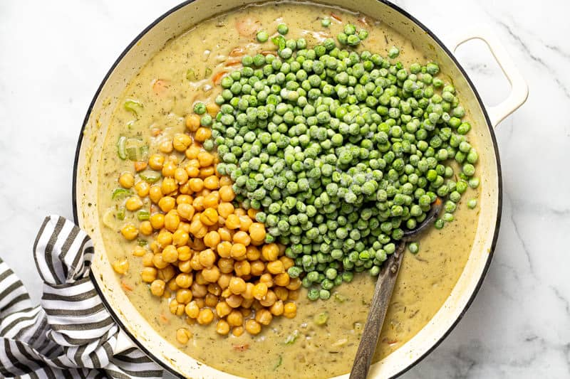 Chickpeas and peas being added to pot pie filling