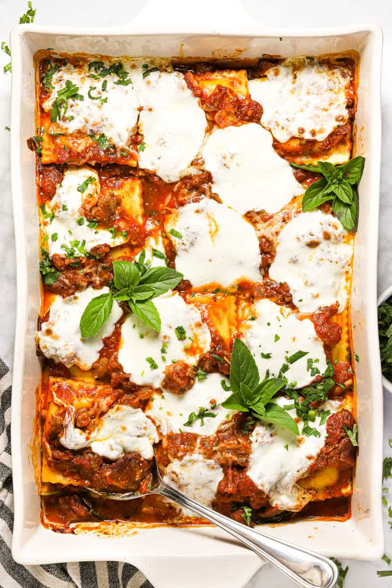 Large white baking dish filled with ravioli sausage and cheese lasagna garnished with fresh basil