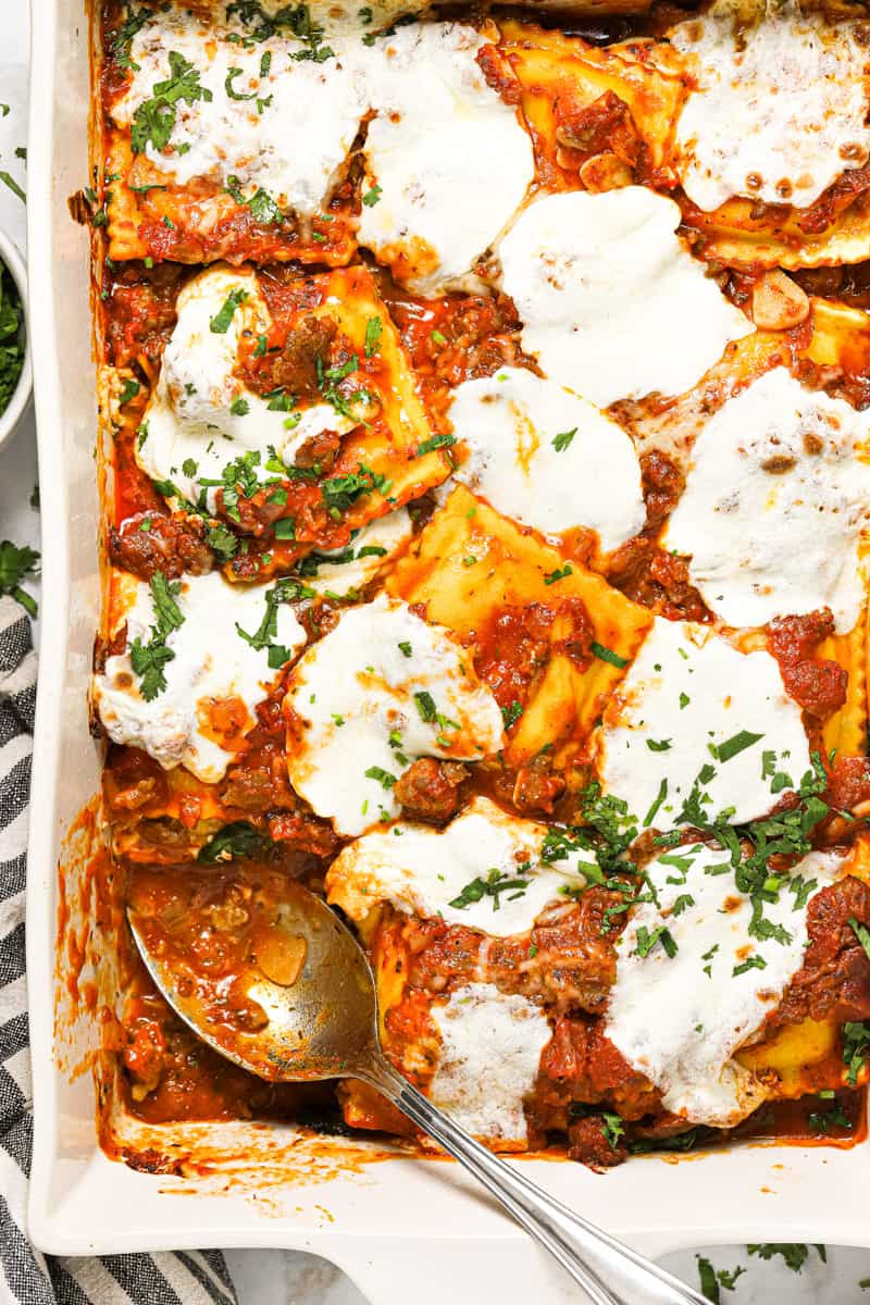 Close up shot of a large white baking dish filled with ravioli sausage and cheese lasagna garnished with fresh basil