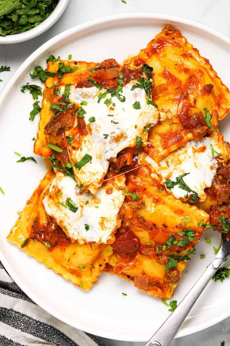 White plate with ravioli sausage and cheese lasagna garnished with fresh basil