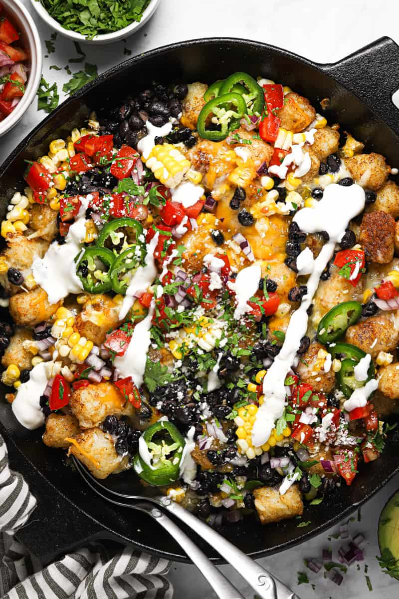 Large cast iron skillet with loaded vegetarian totchos garnished with cilantro and sour cream
