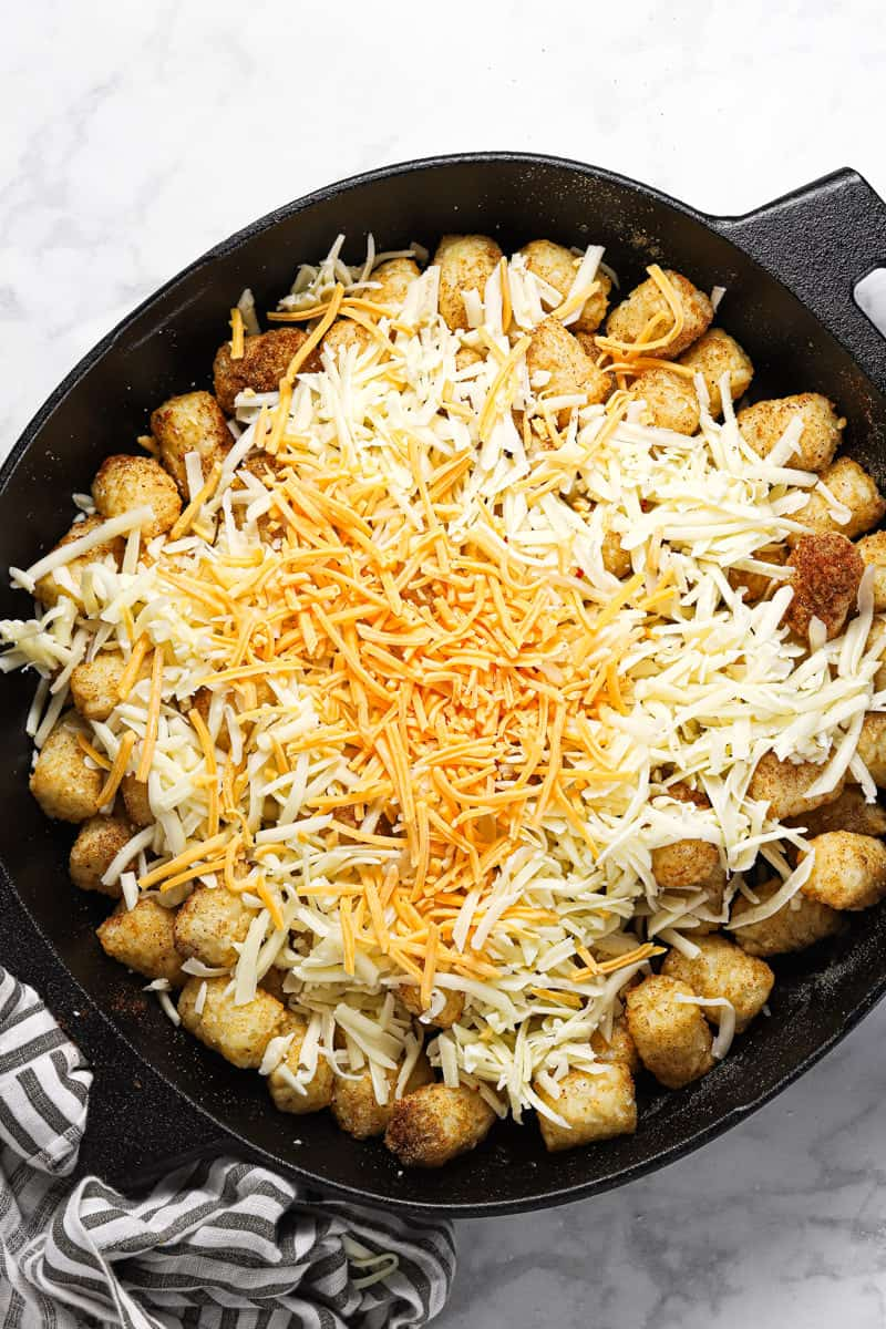 Tater tots in a cast iron skillet topped with shredded cheese