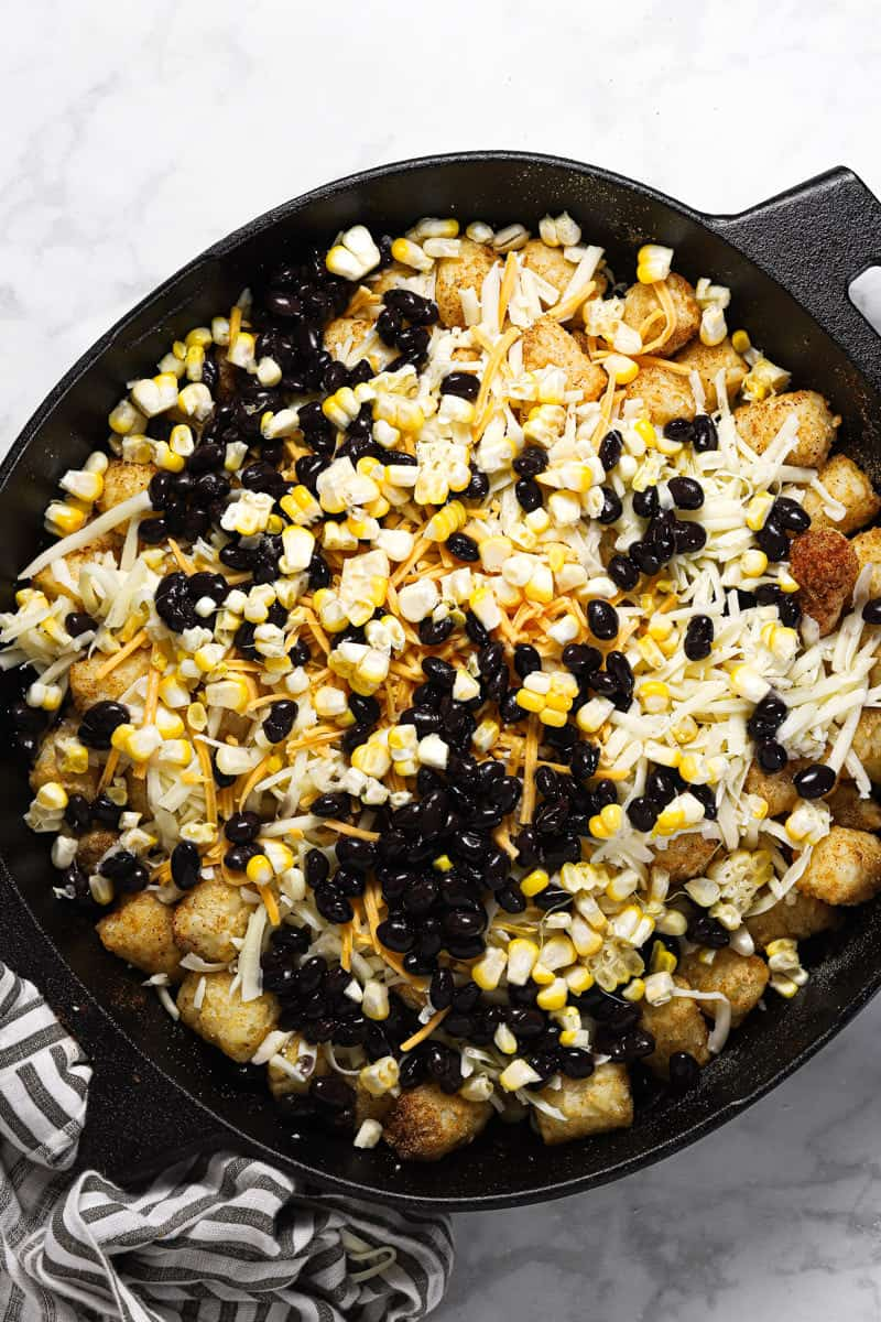 Tater tots in a cast iron skillet topped with cheese black beans and corn