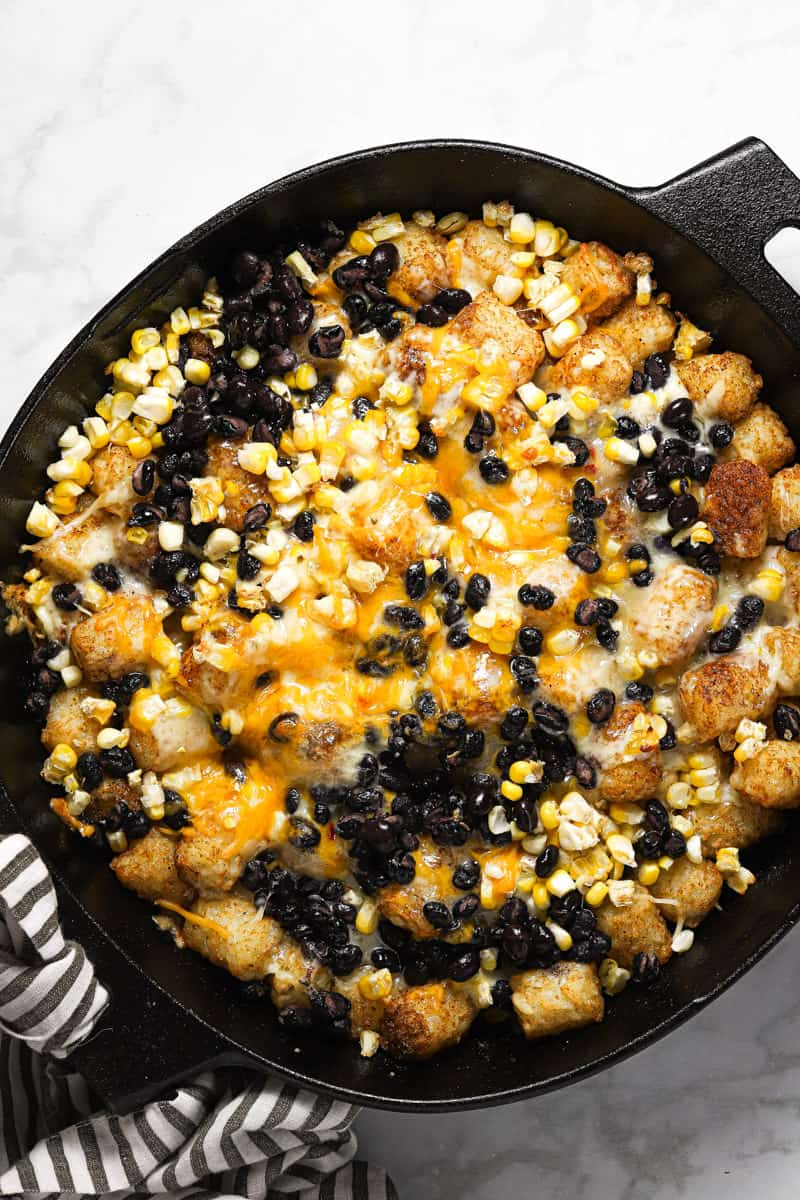 A cast iron skillet filled with freshly baked tater tot nachos
