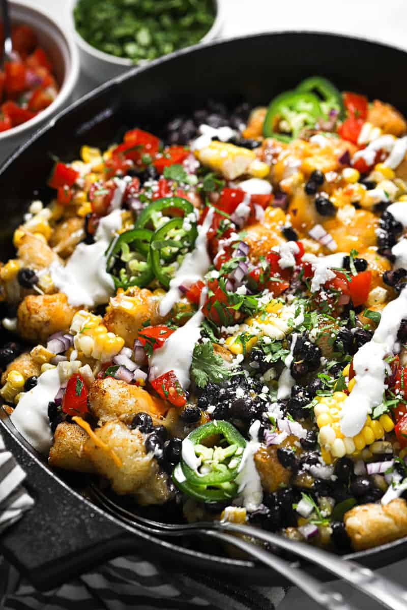 Close up shot of a cast iron skillet with loaded vegetarian totchos garnished with cilantro and sour cream