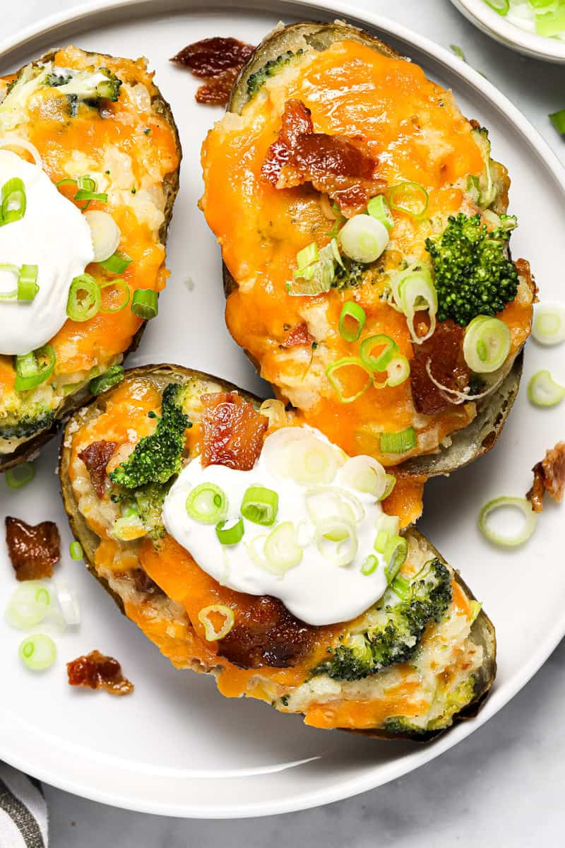 White plate with three twice baked potatoes garnished with sour cream and sliced green onion