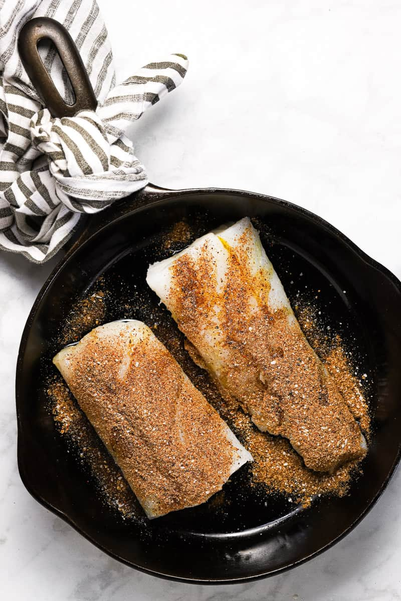 Black cast iron pan with seasoned cod for fish tacos