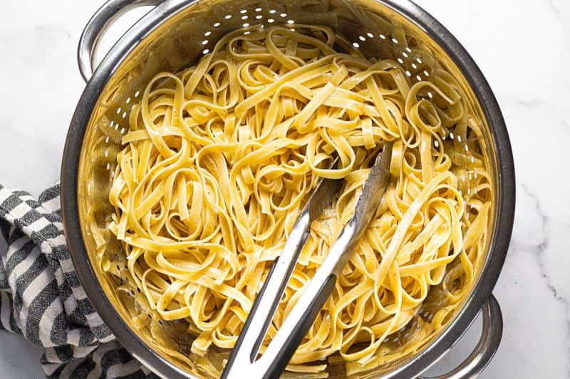 metal strainer with al dente fettuccine noodles