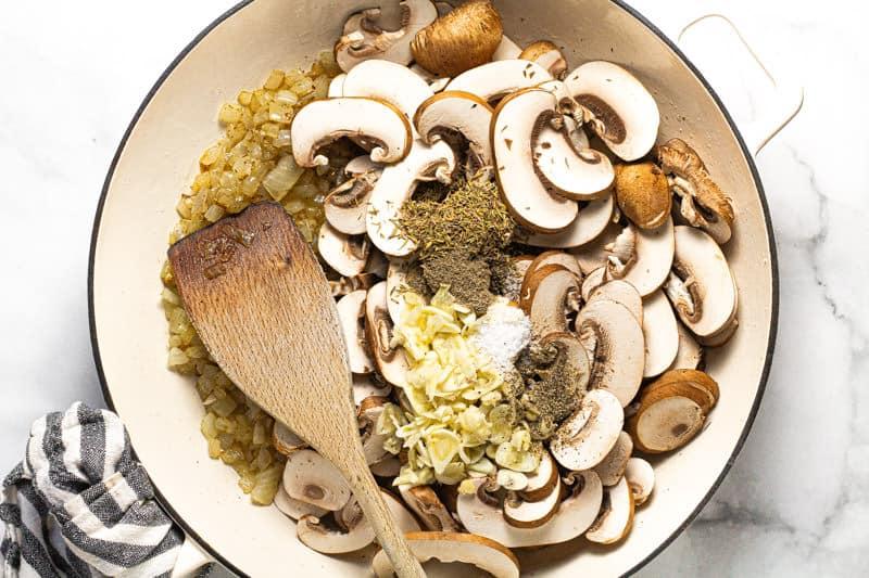 Large white pan with sauteed onion sliced mushroom fresh garlic and herbs