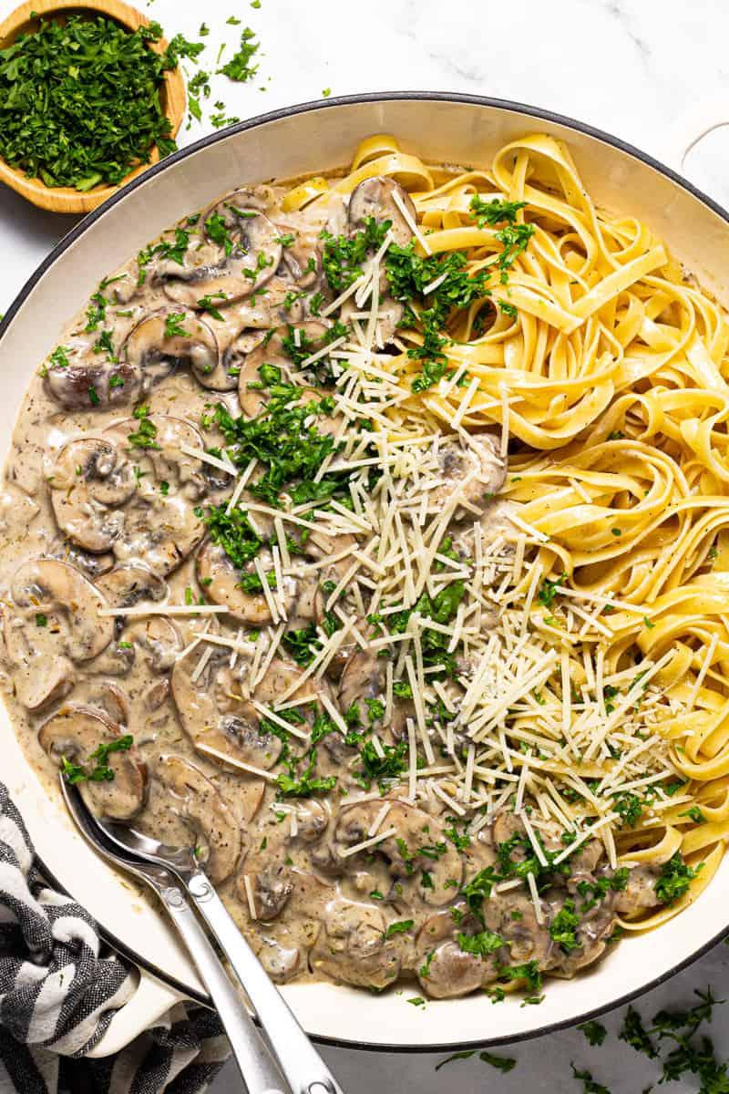 Large white pan filled with vegan mushroom stroganoff garnished with fresh chopped parsley