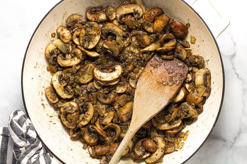 Large white pan with sauteed mushrooms