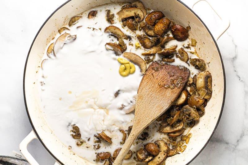 Large white pan with sauteed mushrooms coconut milk and Dijon mustard
