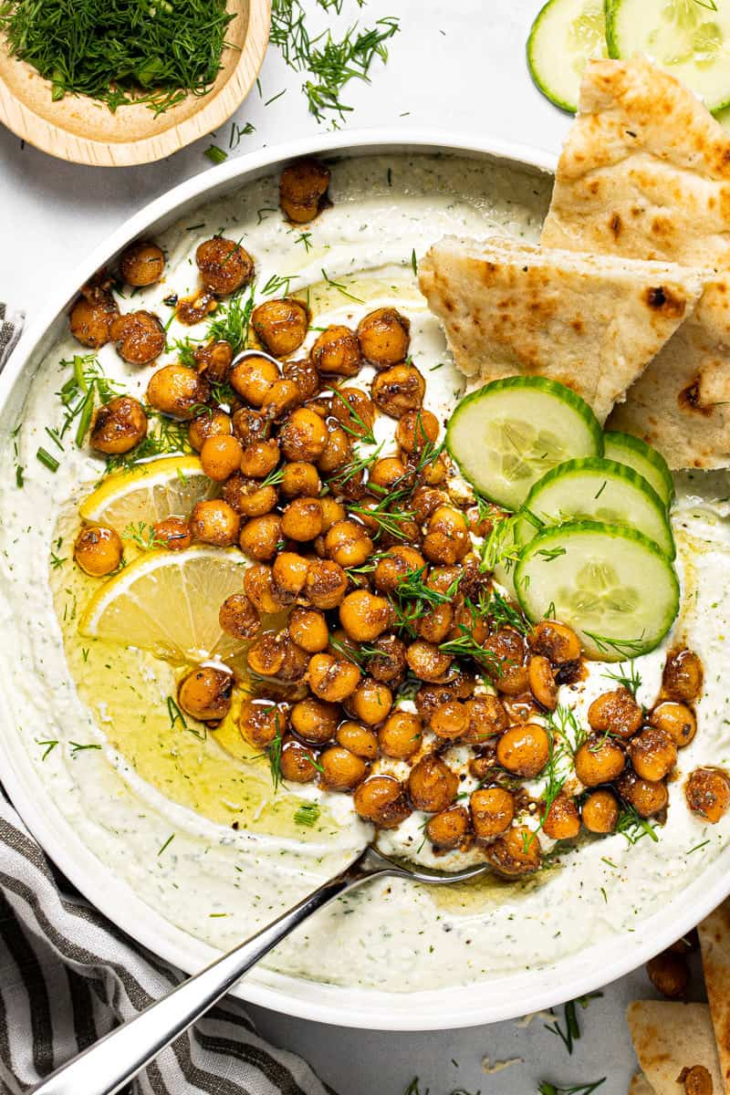 Close up shot of a white bowl filled with whipped feta topped with chickpeas