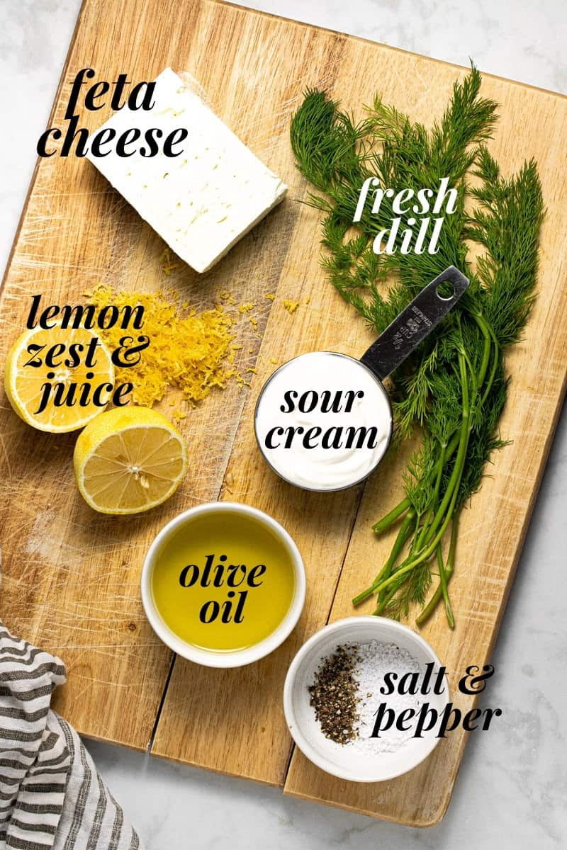 Wooden cutting board with ingredients to make whipped feta dip