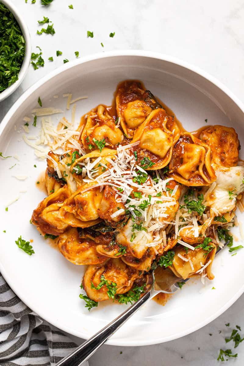 White bowl with a large scoop of baked tortellini garnished with fresh chopped parsley