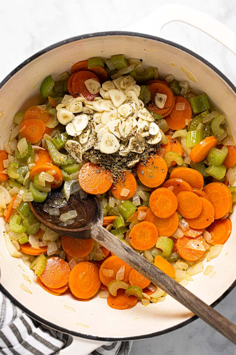 Large white pot with sautéed carrots celery onion with garlic and herbs