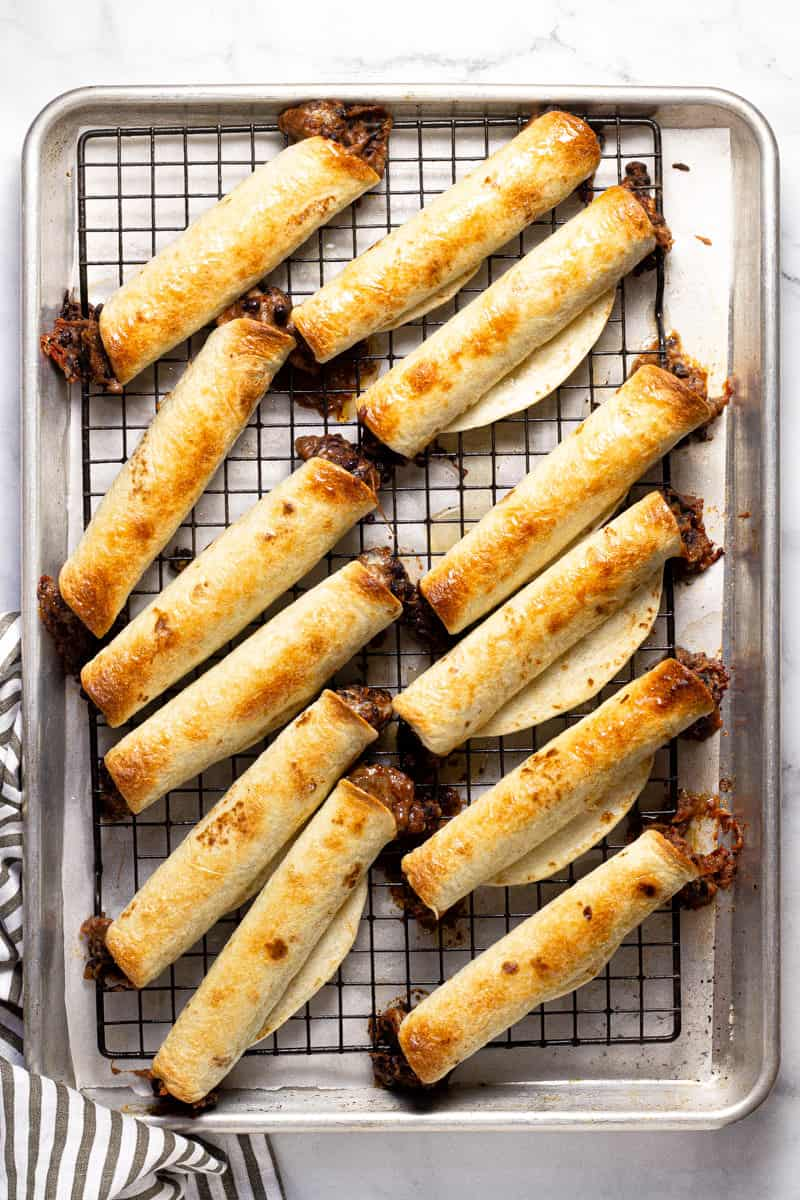 Baking sheet with freshly baked homemade black bean flautas