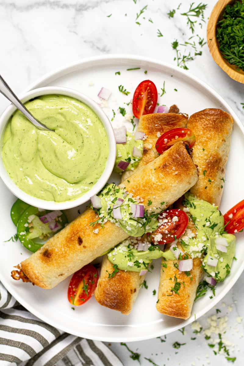 White plate with three baked flautas garnished with fresh cilantro and avocado cream sauce