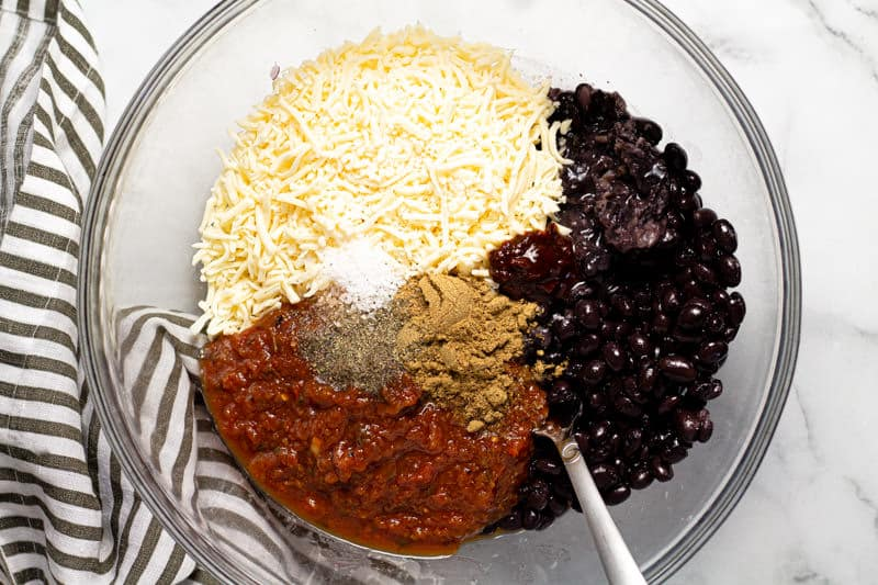 A glass bowl filled with ingredients to make the filling for black bean flautas