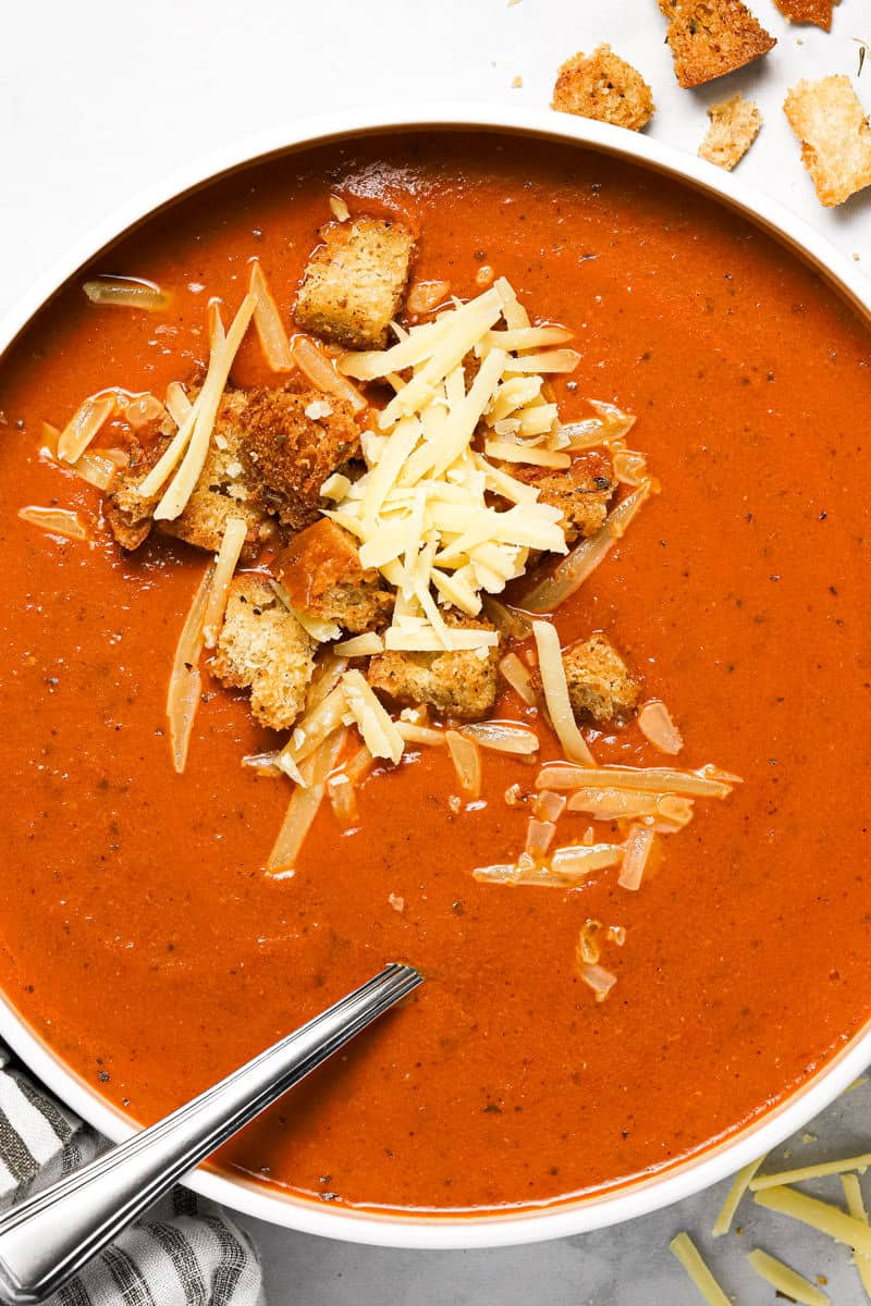 Overhead shot of a white bowl filled with homemade tomato basil soup garnished croutons and cheese