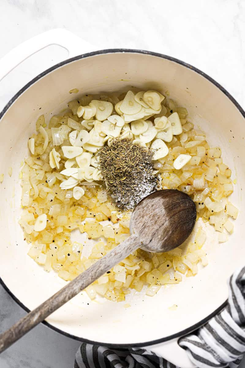 Large white pot with sautéed onion fresh sliced garlic and dried herbs