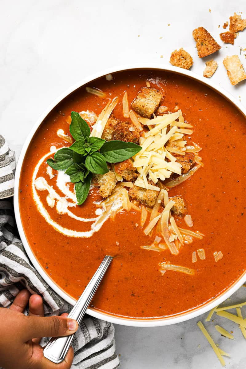 Overhead shot of a white bowl filled with homemade tomato basil soup garnished with fresh basil leaves