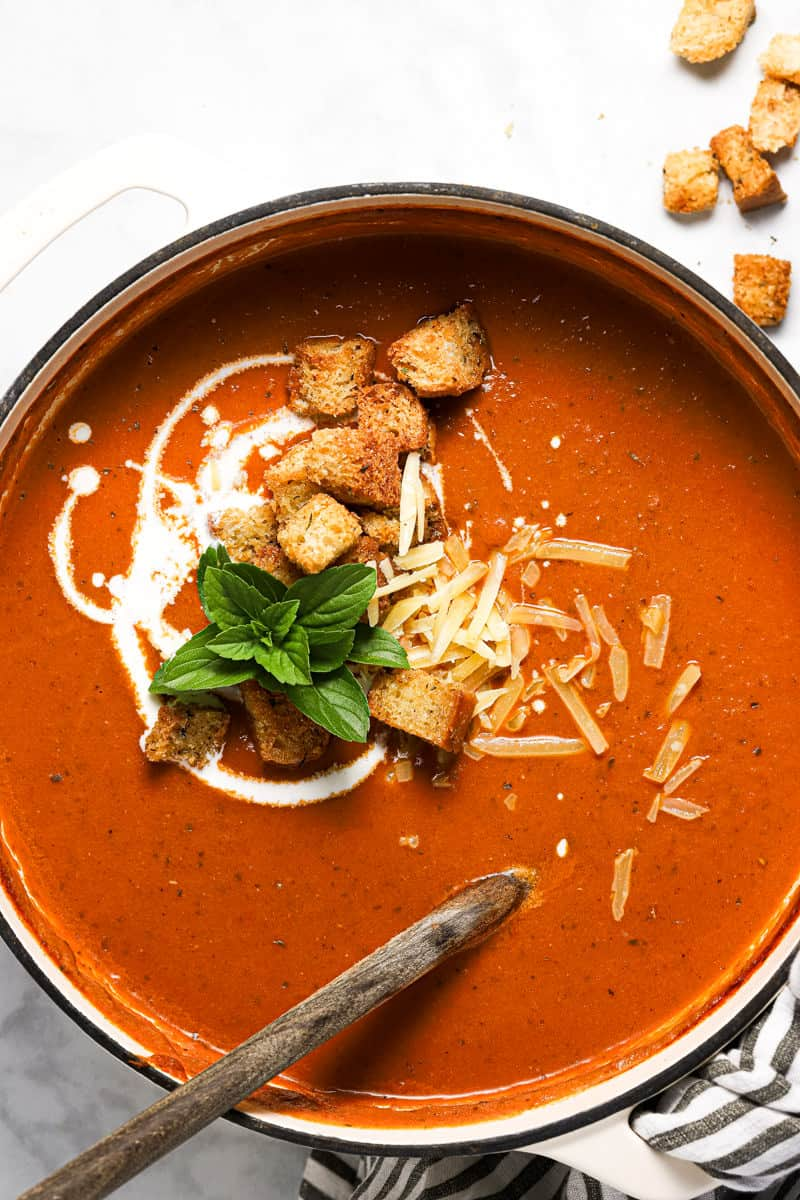 Overhead shot of a white pot filled with homemade tomato basil soup garnished with fresh basil leaves