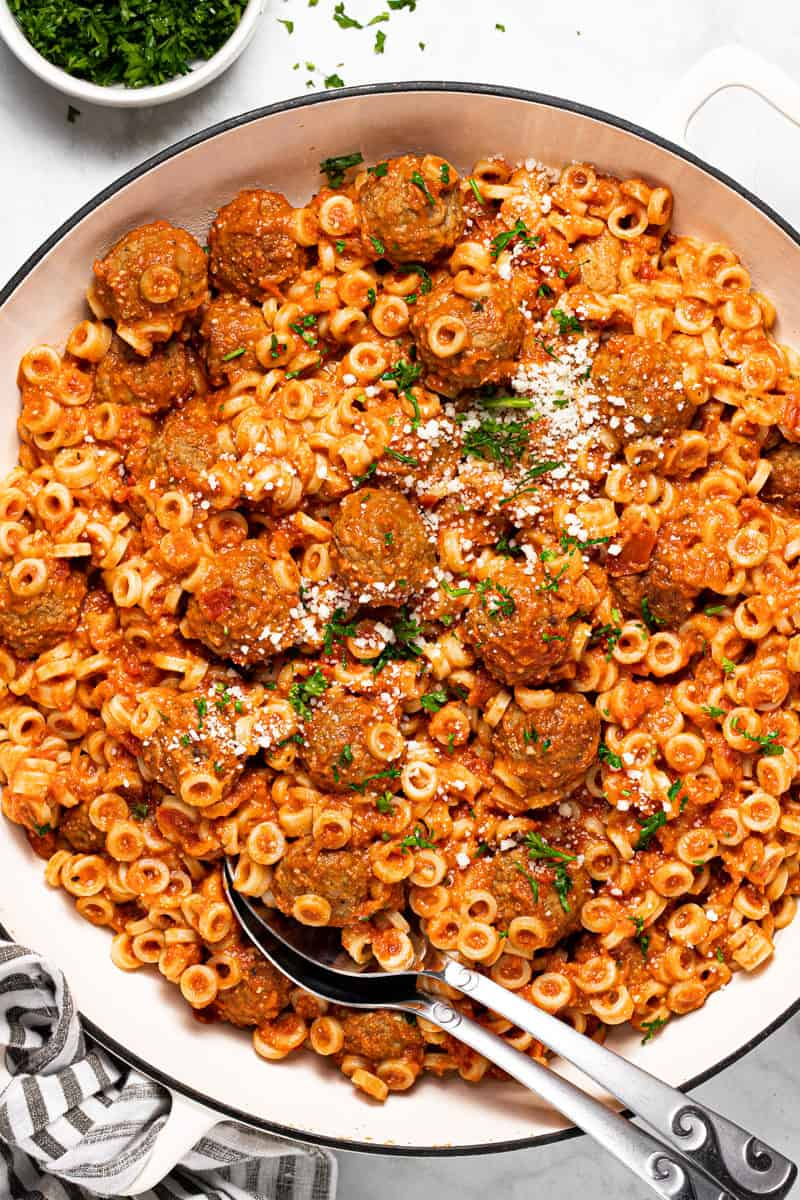 Large white pan filled with homemade spaghettios garnished with Parmesan and parsley