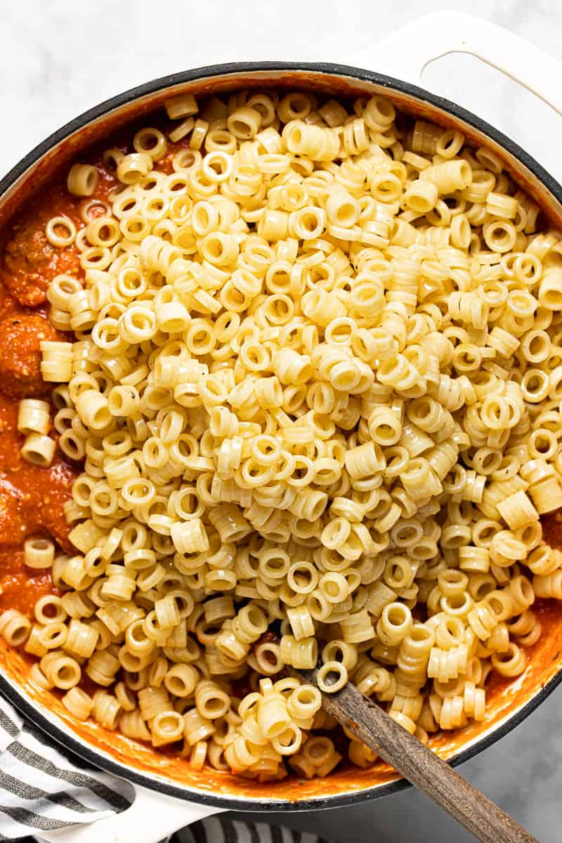 Ring noodles being added to cheesy tomato sauce and meatballs