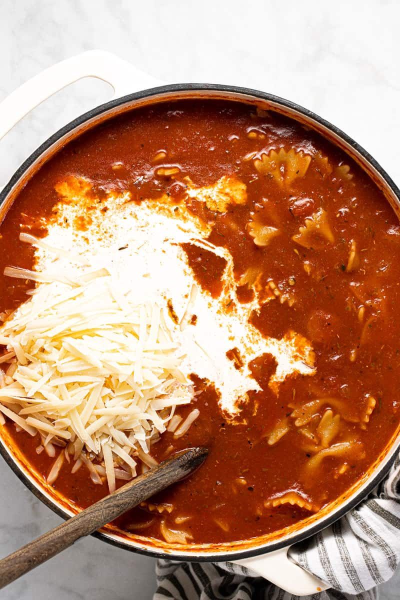 White pot filled with lasagna soup with Parmesan and cream being added
