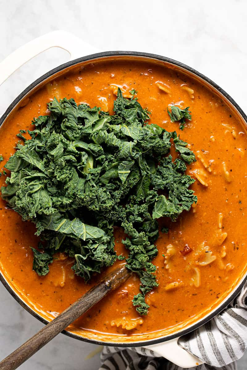 Lasagna soup in a pot with chopped kale being added
