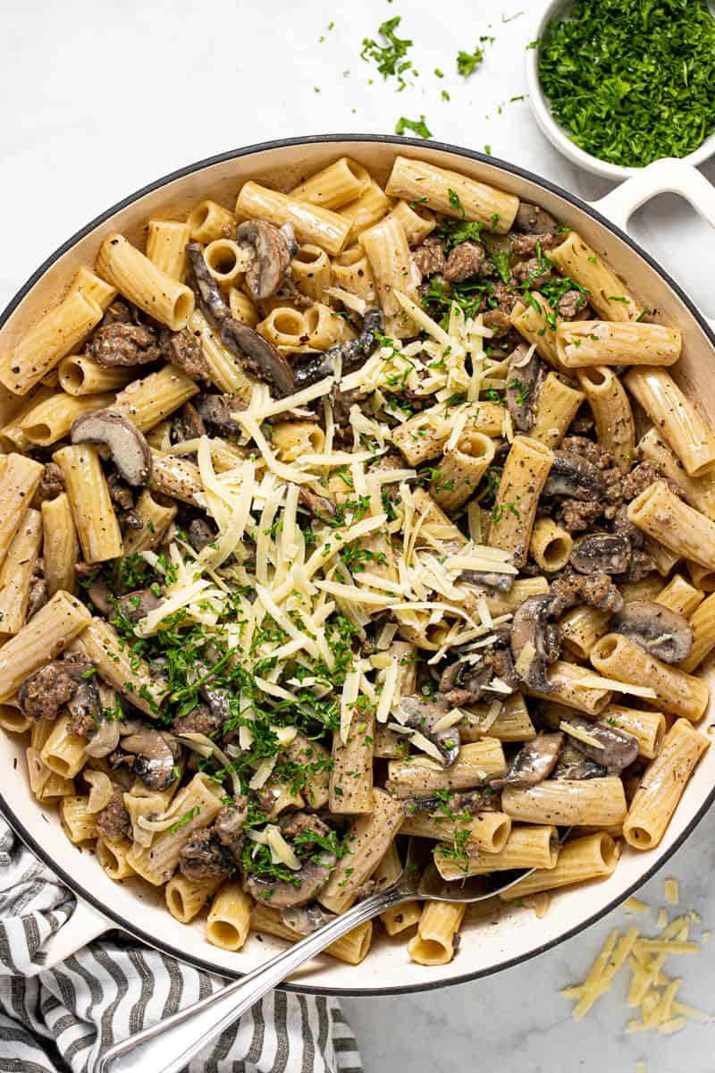 Large pan filled with creamy sausage and mushroom pasta garnished with Parmesan and red pepper flakes