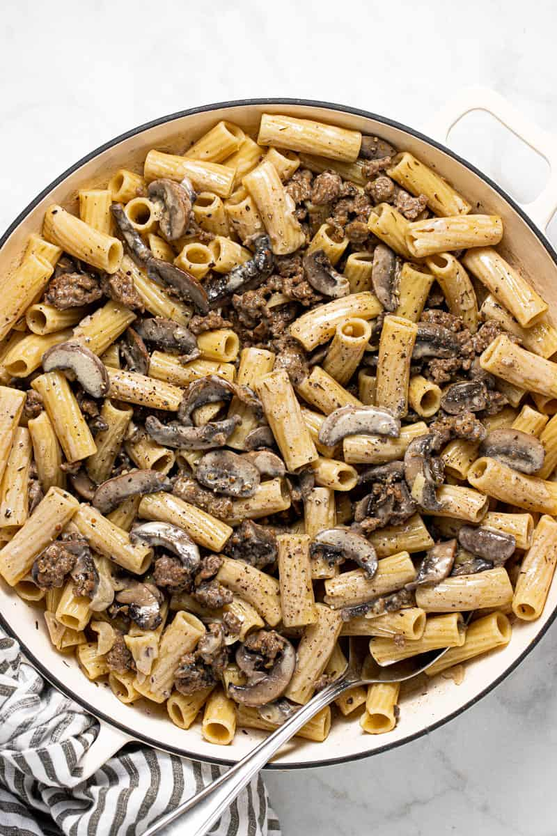 Large pan filled with creamy sausage and mushroom pasta