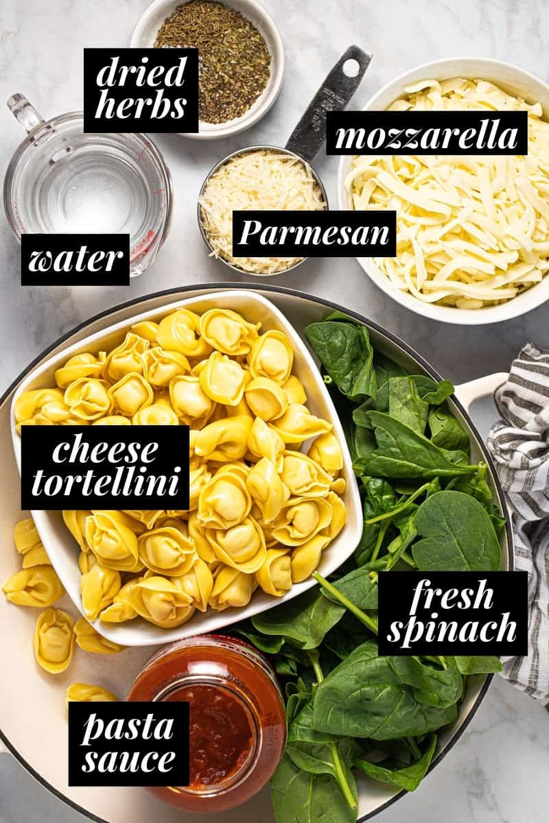 White marble counter top with ingredients to make baked tortellini casserole