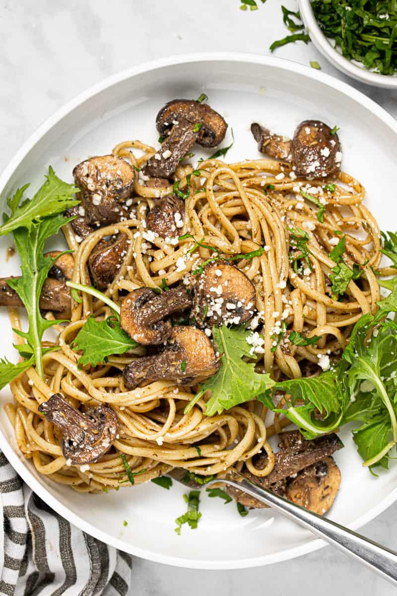 Large white bowl filled with balsamic mushroom linguine garnished with fresh parsley