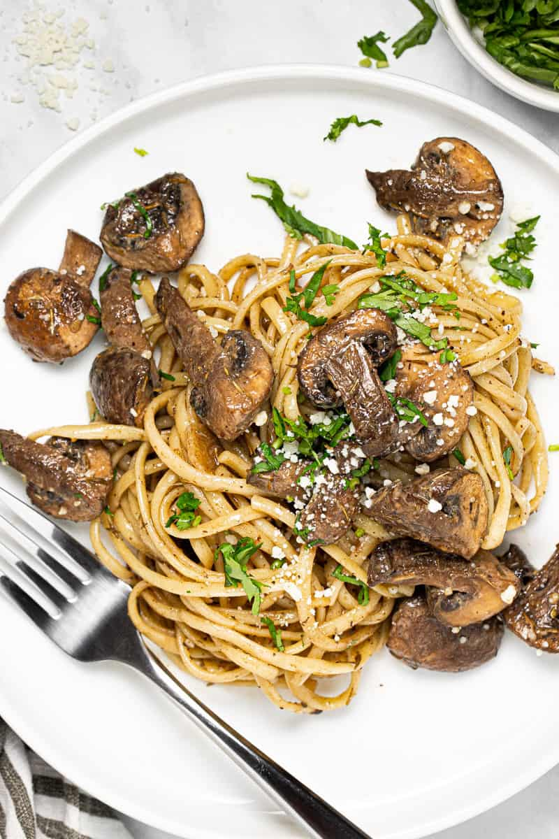 Large white plate filled with balsamic mushroom linguine garnished with fresh parsley