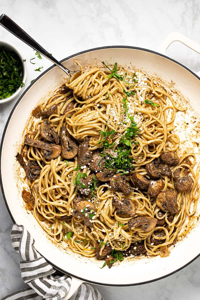Lage white pan filled with balsamic mushroom linguine garnished with fresh parsley