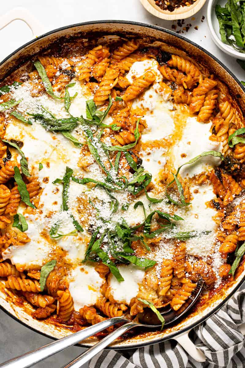 Large white pan filled with baked rotini topped with melted mozzarella and garnished with fresh basil