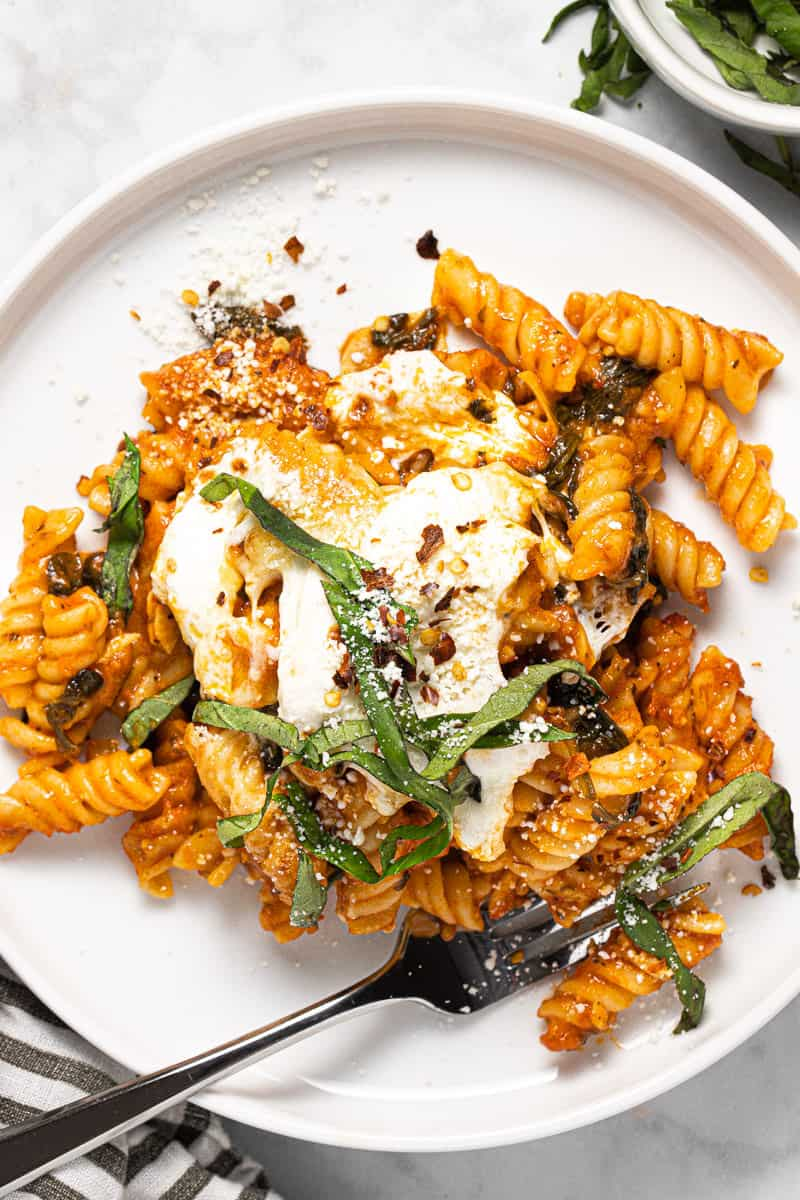 White plate filled with no boil baked pasta garnished with Parmesan and basil