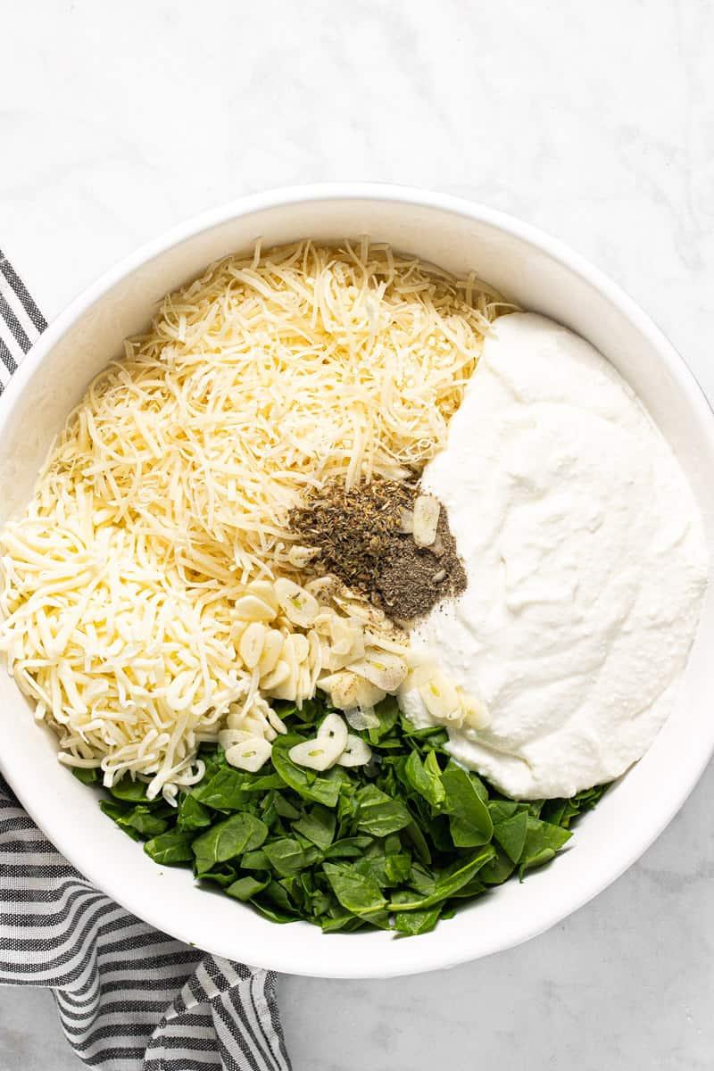 Large white bowl with ingredients to make lasagna filling