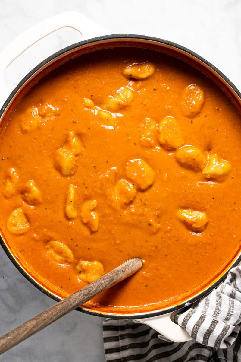 Large white pot filled with homemade tomato gnocchi soup
