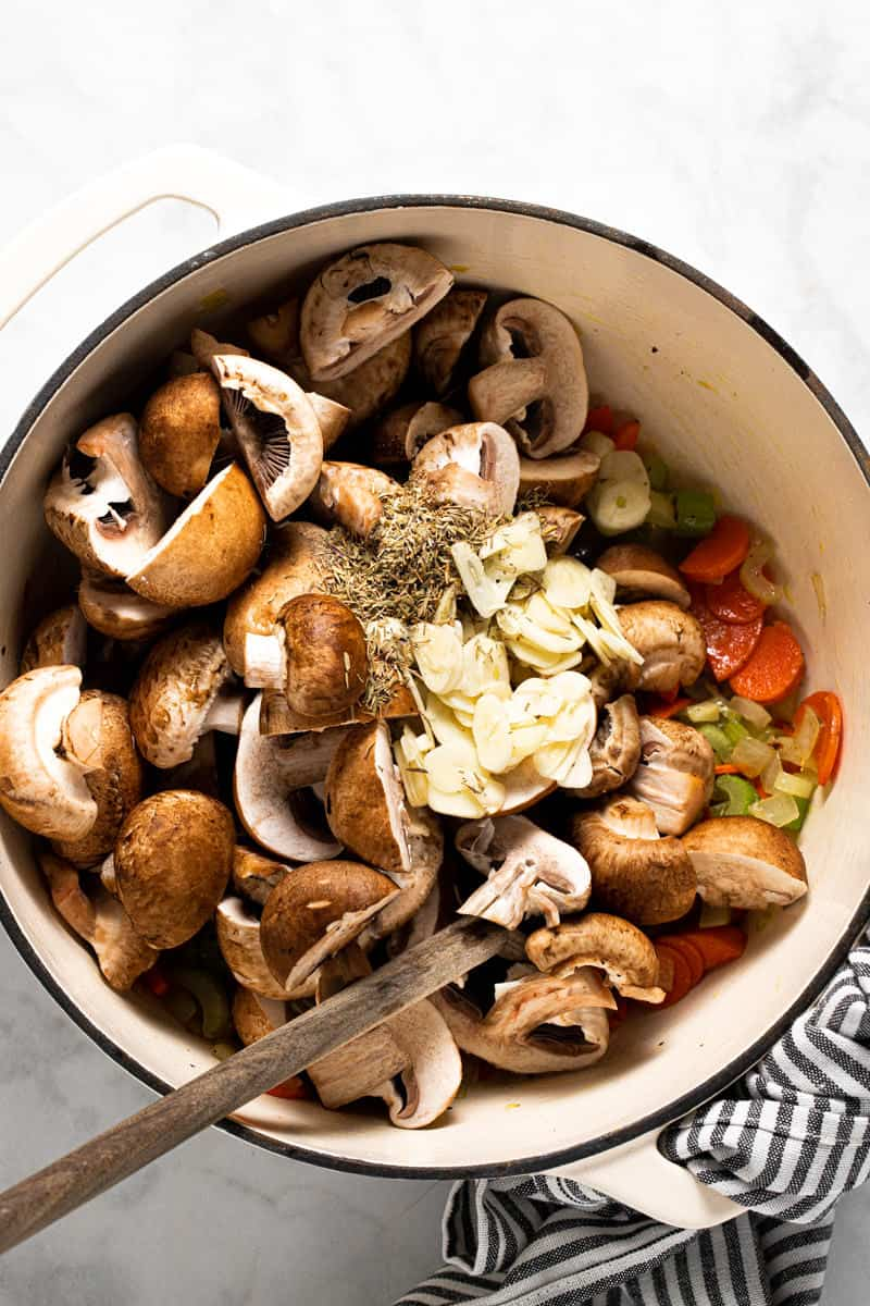 Large white pot filled with chopped veggies sliced garlic and dried herbs