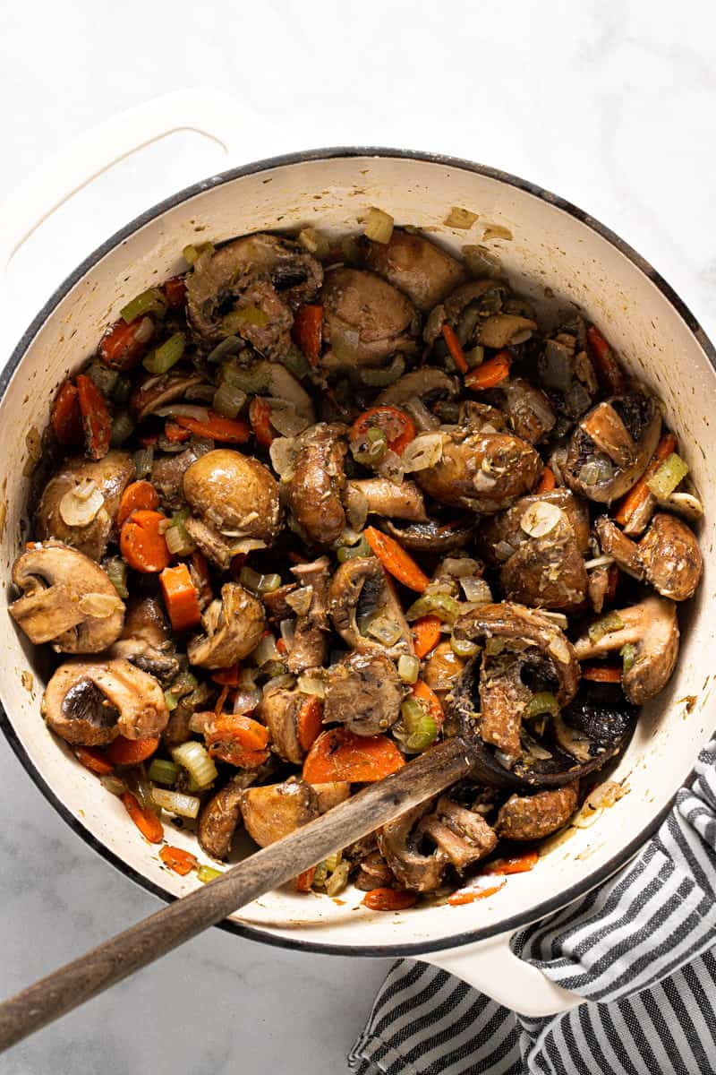 Large white pot filled with ingredients to make a vegetable stew recipe