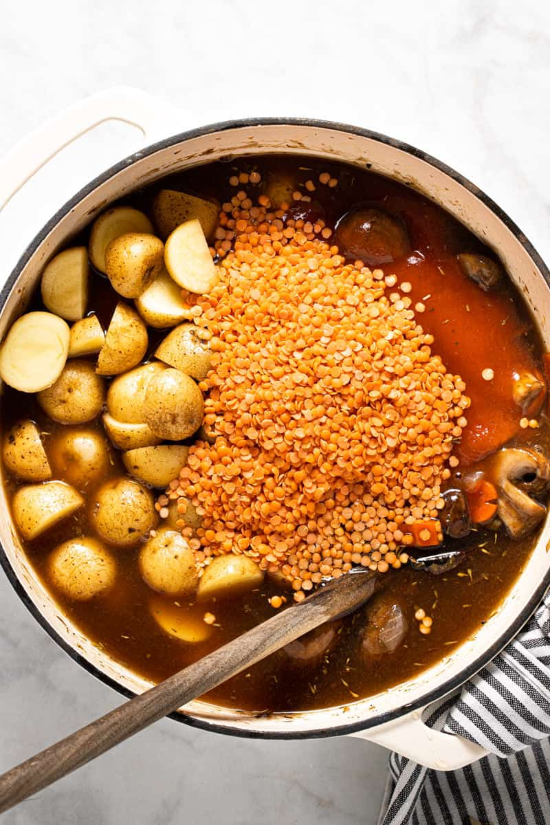 Large white pot filled with ingredients to make this vegetable stew recipe