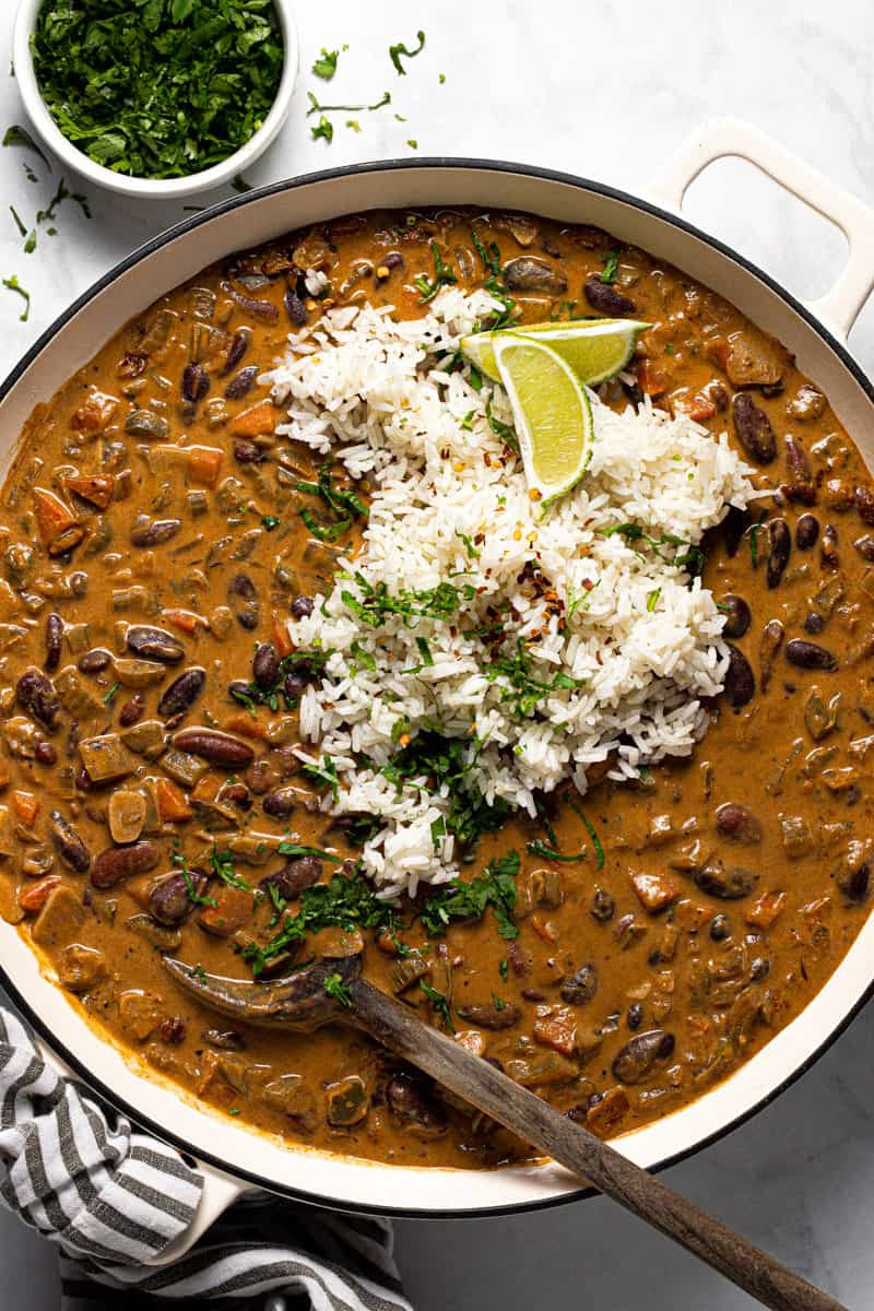 Large white pot filled with red beans and rice garnished with fresh cilantro