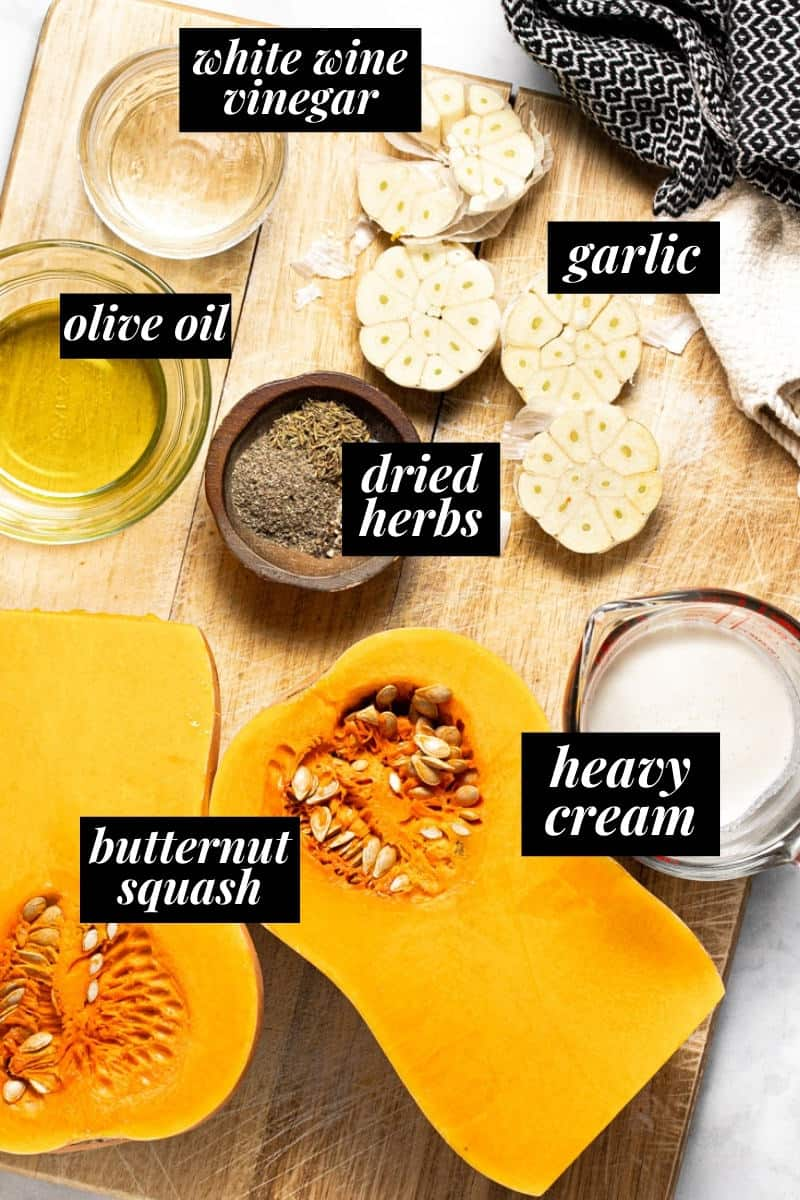 A large wooden cutting board with ingredients to make roasted squash and garlic cream sauce