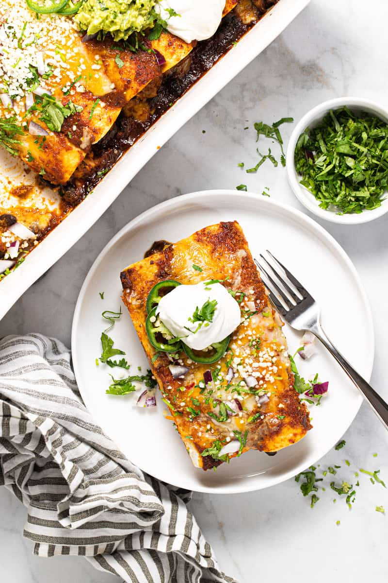 White plate with two cheesy chicken enchiladas topped with sour cream and cilantro