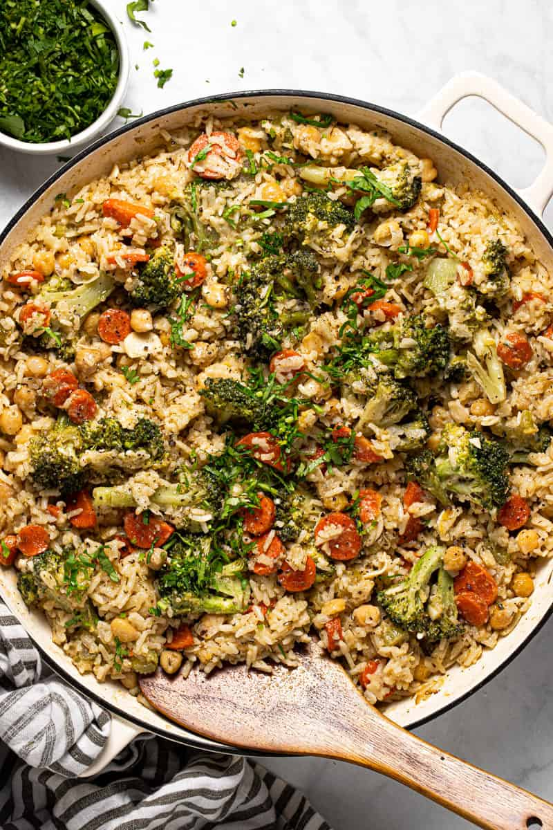 Large white pan filled with cheesy chickpeas and rice casserole garnished with fresh parsley