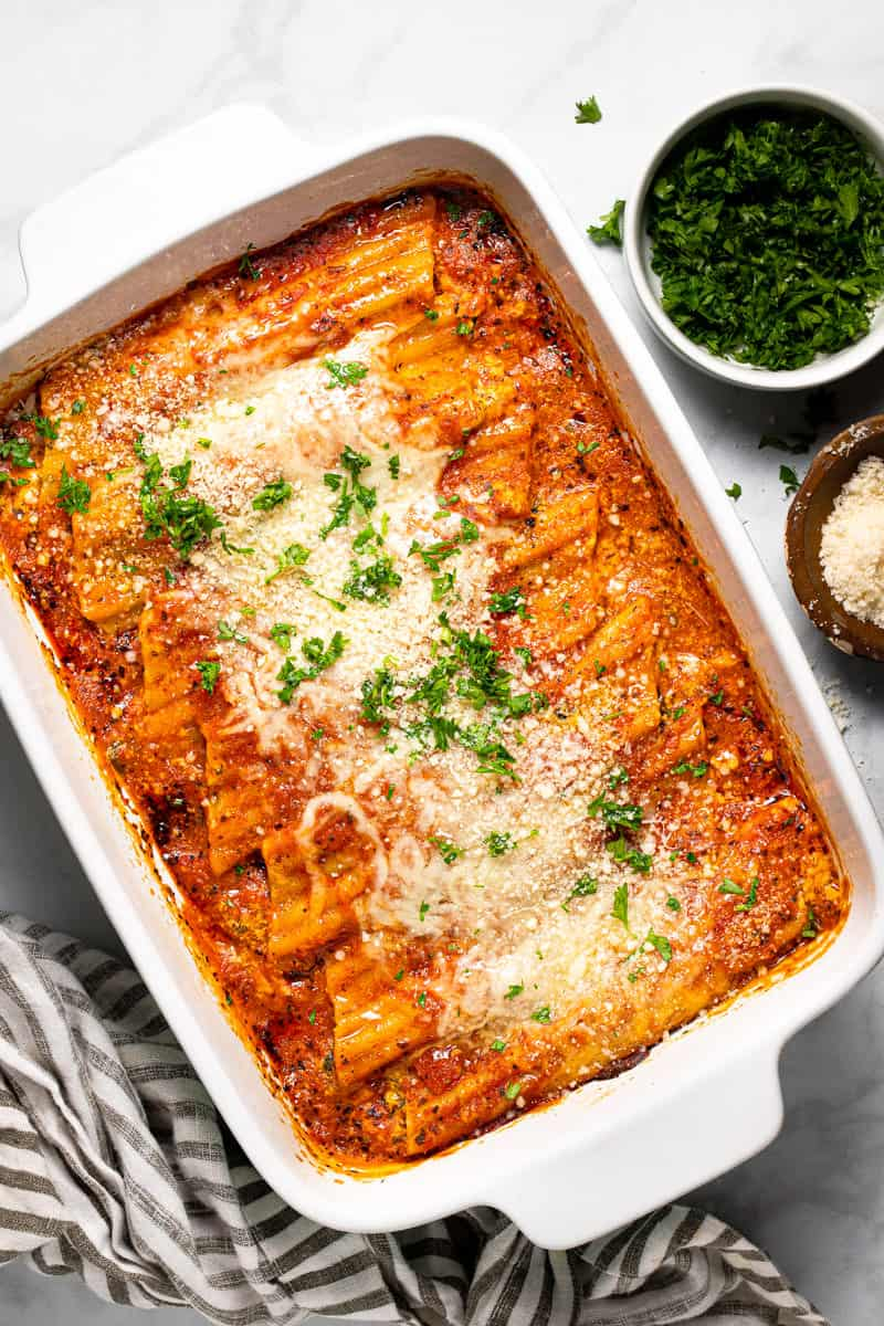 Large white baking dish filled with homemade cheesy baked manicotti garnished with fresh parsley