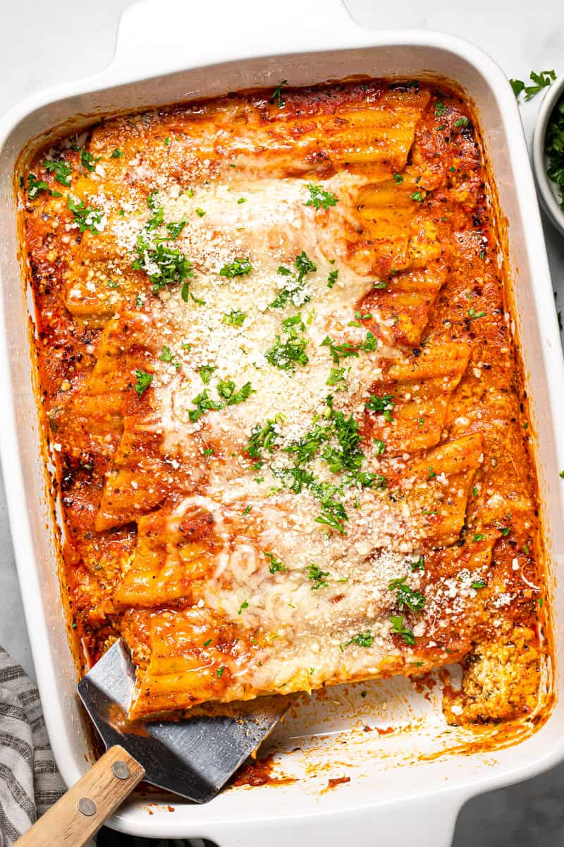 Large white baking dish filled with homemade cheesy baked manicotti garnished with fresh parsley